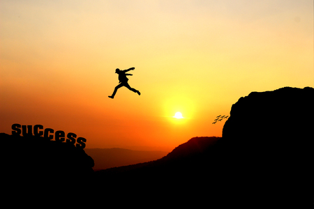 Silhouette of a man jumping over the cliff, jump go on to success
