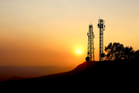 sylwetka słupa energii elektrycznej, wieża telekomunikacyjna z zachodem słońca na tle nieba.