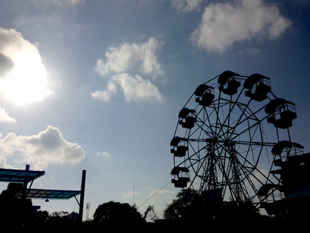 silhouette of Amusement Park with the sun and sky.