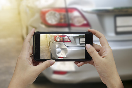 Hand holding smart phone take a photo at The scene of a car crash, car accident for insurance.