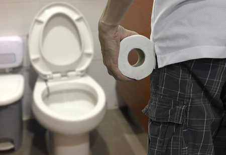 Hand holding toilet paper roll and Entering the toilet Фото со стока