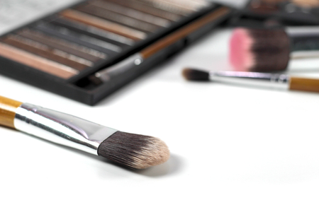 Close up makeup brushes with eye shadows palette and brushes background. Фото со стока