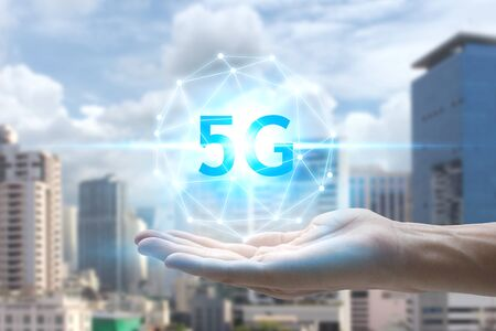 hand holding network using 5G technology with virtual screen on the city background, Technology Internet 5G global network concept. Standard-Bild