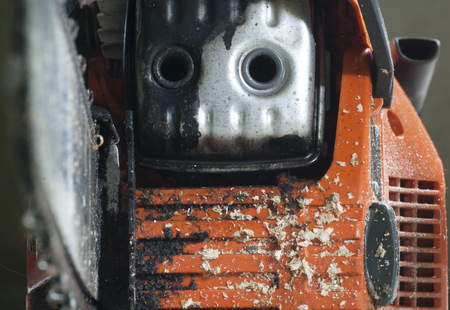 The front of a used chainsaw, covered in sawdust. Zdjęcie Seryjne