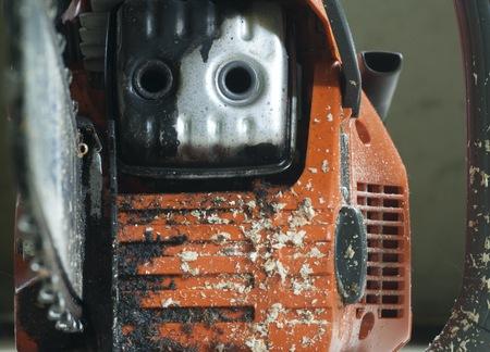 La parte anteriore di una motosega usata, coperto di segatura. Archivio Fotografico - 41027016