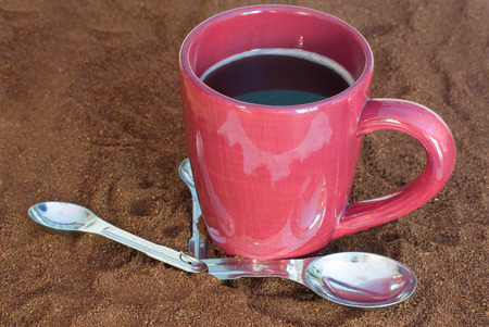 Cup of coffee, and measuring spoons, on fine ground coffee beans Stok Fotoğraf