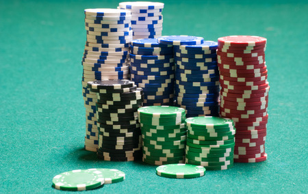 holdem: Poker chips on green felt surface
