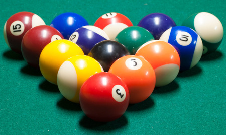 table surface: Racked billiards balls, on a green felt playing surface