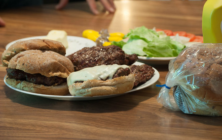 Burgers, and vegetables, on a kitchen table, ready for eating. Banco de Imagens