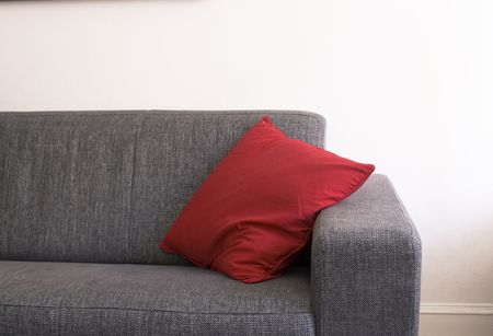couch with red pillow