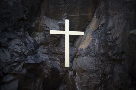Religious cross on a stone wall