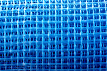 The blue reinforced mesh rolled into a roll lies on the ground. Construction resource to strengthen the walls in the process of their insulation. The grid is placed on the right side. Copy space.