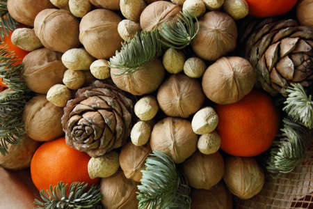 Gift Christmas bouquet. Pine cones, oranges, peanuts, walnuts, spruce branch in a beautiful package. Electoral focus. Christmas and New Year is theme. Holiday theme. Background. Food
