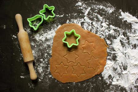 Do it yourself ginger biscuits. Step-by-step cooking recipe. Step 7 on cut special cookie shapes. Christmas atmosphere. Cooking ginger biscuits. Holiday. Instruction. On a black background.