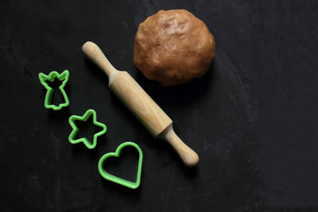 A dough ball, a rolling pin for dough and a cookie shape on a black background. View from above. Cooking ginger biscuits. Christmas atmosphere. Flatlay. Copy space for text. Pastries. Holiday.