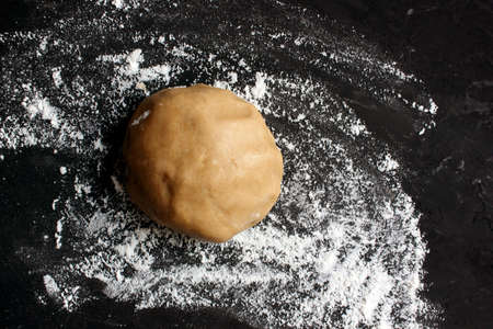 Ginger cookie dough on floured black surface. View from above. The dough has brown tint. Cooking ginger biscuits. Christmas atmosphere. Ball of dough. Copy space for text, Homemade pastries. Holiday.
