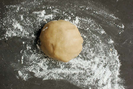 Ginger cookie dough on floured black surface. View from above. The dough has brown tint. Cooking ginger biscuits. Christmas atmosphere. Ball of dough. Copy space for text, Homemade pastries. Holiday. Reklamní fotografie