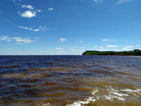 Volga River. Kamsky Estuary, Russia. Beach in the distance. The shore, near the river with trees. Part of the coast is stone. A clear, sunny day, blue sky with clouds. Copy space. Landmark. Landscape Banco de Imagens