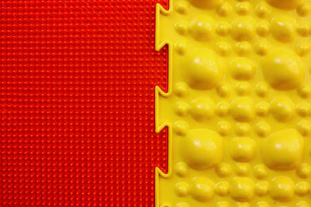 Two orthopedic mats. Bright colorful multicolored mats to prevent flat feet and foot massage. View from above. Orthopedist. Prevention. The yellow and red mat are joined together.
