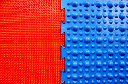 Two orthopedic mats. Bright colorful multicolored mats to prevent flat feet and foot massage. View from above. Orthopedist. Prevention. Red and blue mat are connected together.