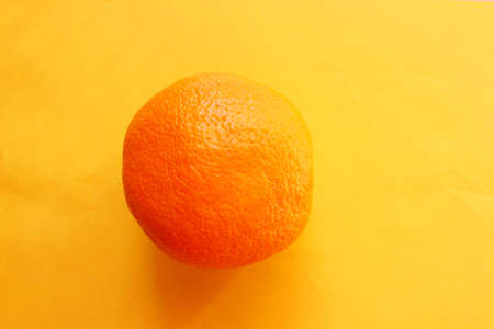 A ripe orange isolated on an orange background. View from above. Vitamin C. Stock Photo