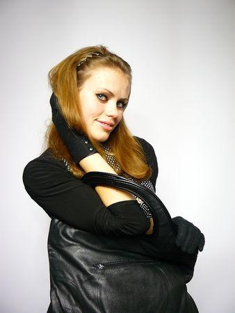 Brown-Haired femme dans une robe avec un sac de cuir noir Banque d'images