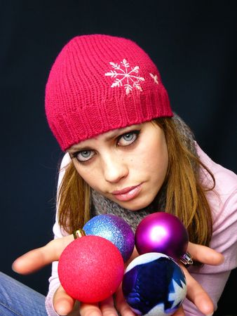 young girl in a cap holds New Years toys