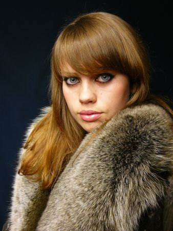 very beautiful girl in a fur coat on darkly dark blue background photo