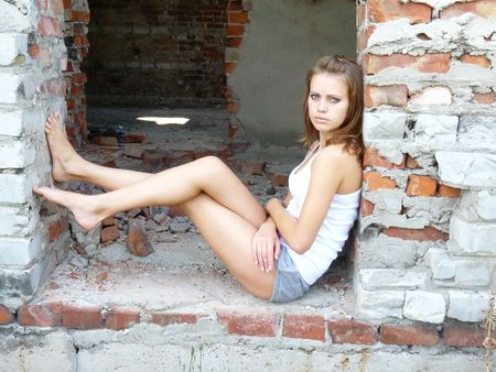 brown-haired woman has sat down to have a rest on ruins Stock Photo