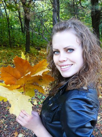 woman holds yellow leaves of a maple in a hand