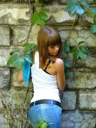 timid young girl costs near a wall and looks downwards Stock Photo