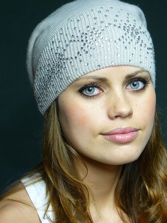 pastes: young blue-eyed girl in a grey cap with pastes  Stock Photo