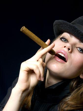 Dame progressive dans un chapeau et une cigarette dans une main.