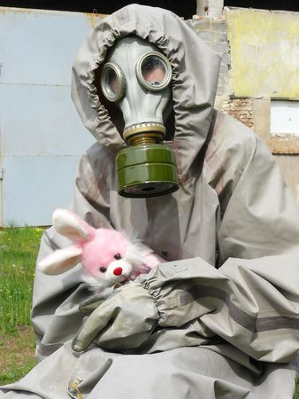 girl in an antigas package and with a toy in hands photo