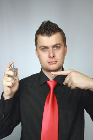 eau de toilette: man in a black shirt holds spirits in a hand Stock Photo