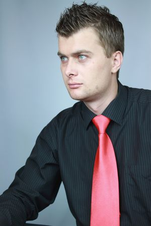 Young businessman in a black shirt in a red tie