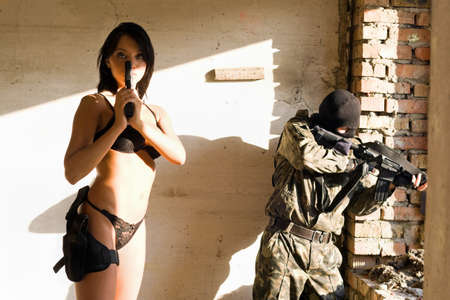 Young woman with gun and soldier. Focus on woman photo