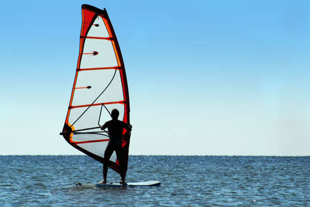 Silhouette of a windsurfer on the sea surface