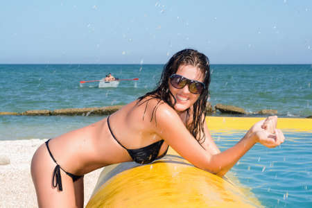 Cheerful sexy young woman by the yellow pool photo