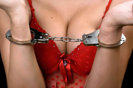 Sexy young woman in red lingerie handcuffed