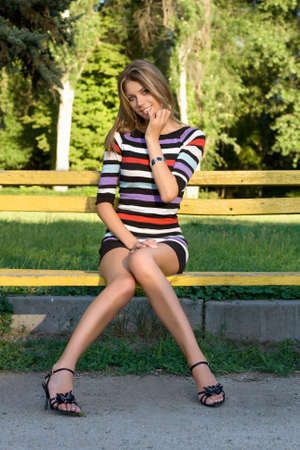 Playful young blonde sitting on a park bench Stock Photo