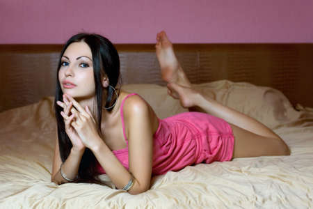 Seductive young brunette lying on the bed photo