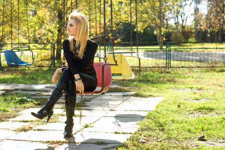 Young pretty blonde sitting on a carousel outdoors photo