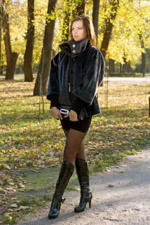 Sexy young woman walking in autumn park photo