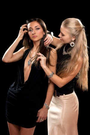 slinky: Two pretty young women. Isolated on black