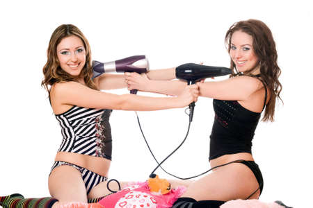 Two playful girlfriends with hair dryers. Isolated on white photo