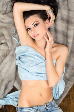Sensual sexy young woman lying on grey fur photo