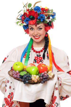 Young woman in the Ukrainian national clothes with fruit. Isolated photo