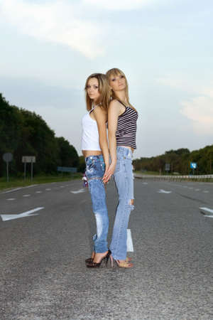 2 way: Two beautiful girls standing on a road