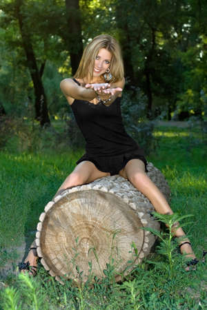 felled: Playful young blonde sitting on a felled trunk tree Stock Photo